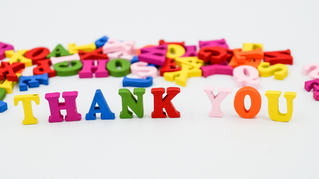 The phrase Thank you on white background and many colorful wooden latters.