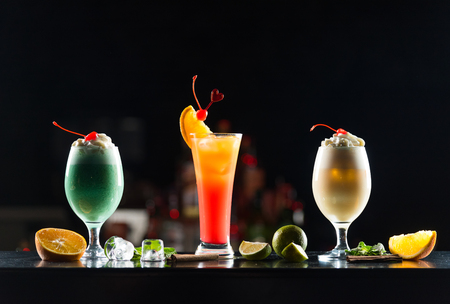 Multi-colored alcoholic cocktails with citrus and berries in glasses of different shapes on the bar.