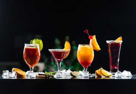 Multi-colored alcoholic cocktails with citrus in glasses of different shapes on the bar.