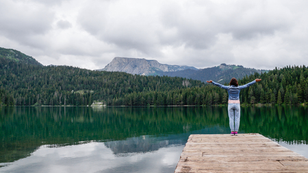 The girl stands with her hands up on the pier of the black lake in the national park Durmitor. Montenegro.