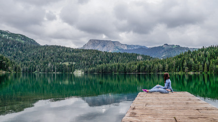 Girl sitting on the dock of the black lake in the Durmitor national park. Montenegro.