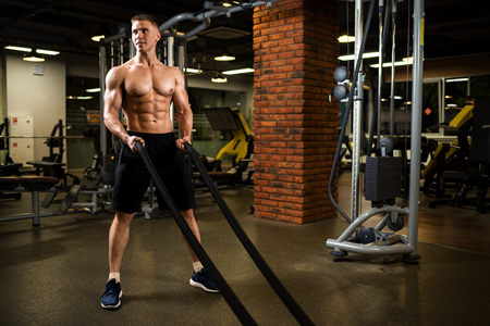 Athletic muscular man torso in the gym. Stock Photo
