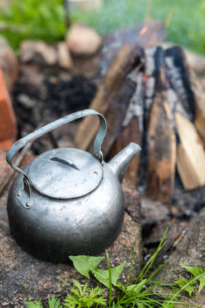 Outdoor picnic kettle with a vintage touch near a bonfire. Cooking outside, campfire cooking.