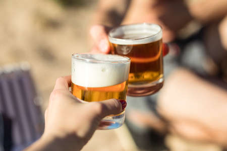 Celebrating life, clinking beer glasses at the beach
