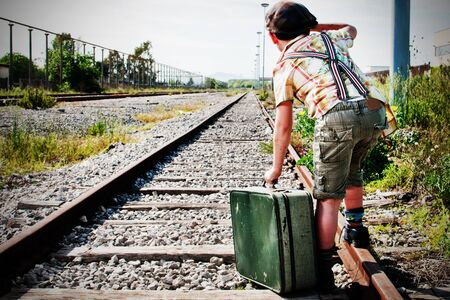 bambino: a child of a railway station, waiting for the train with suitcases