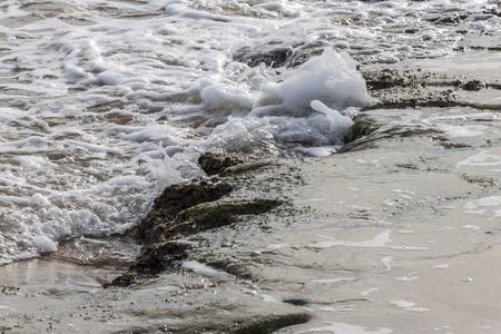 small waves breaking on some rocks on the beach. Guardamar del Segura, Spain Foto de archivo
