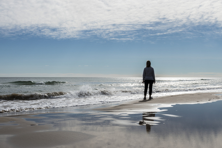 woman looking at the horizon on the shore of the beach. Guardamar del Segura, Spain