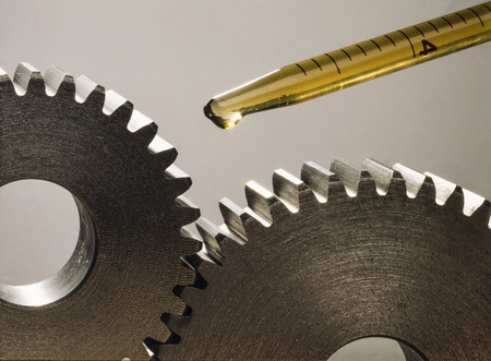Lubricating two pinions with a few drops of oil. Mechanical sprockets Stok Fotoğraf