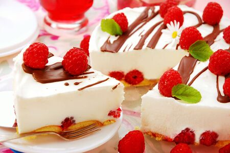 raspberry cake decorated with fresh fruits and melissa leaves photo
