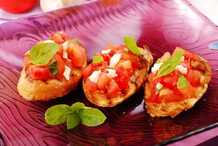 italian bruschetta with tomato,basil and cheese on purple plate photo