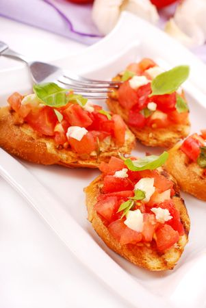 italian bruschetta with tomato,basil and cheese on white plate photo