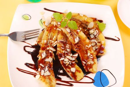 flaked: fried bananas with flaked almonds and chocolate sauce Stock Photo