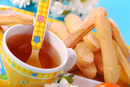 baby with spoon: cup of fruit tea and sponge fingers for child