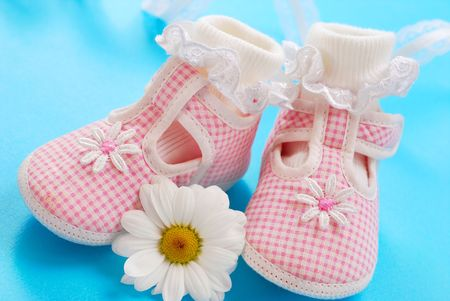 pink baby shoes for little girl on blue background photo