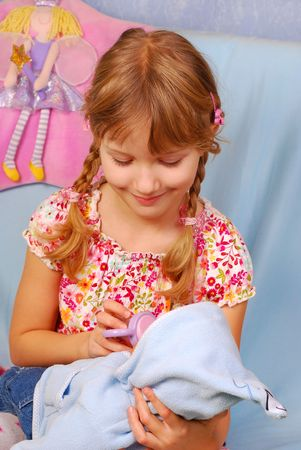 little girl playing with her baby doll pretending mom photo