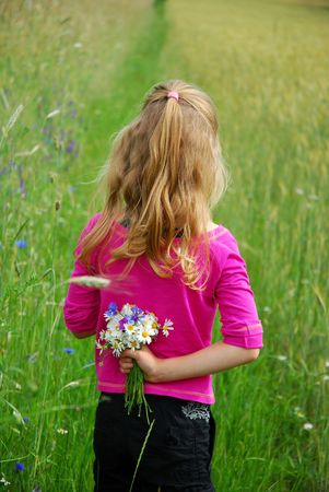 young girl on field with bunch of wild flowers hiding  behind the back Stock Photo - 6488737