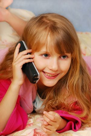 young girl talking by phone on the bed photo