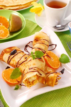 rolled pancakes with cottage cheese and orange poured chocolate photo