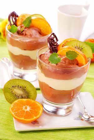 two glasses of chocolate and vanilla dessert with kiwi and orange photo