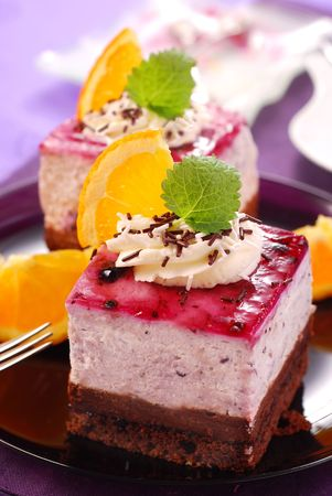two portions of blueberry cake with whipped cream and orange  decoration photo