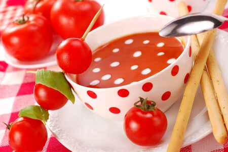 grissini: bowl of tomato soup with cream drops and with grissini