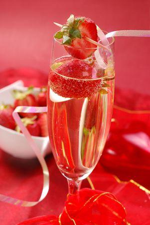 brindisi champagne: Champagne con fragole per party su sfondo rosso