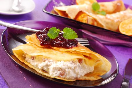 poured: pancakes stuffed with cottage cheese and raisins poured blackcurrant confiture