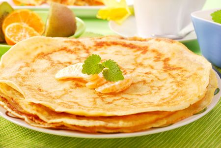 pile of pancakes decorated with orange and melissa Stock Photo