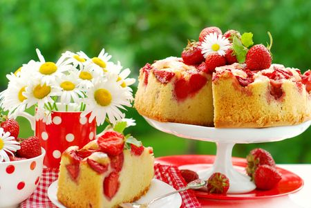 garden party: strawberry sponge cake with fresh fruits decoration on table in the garden