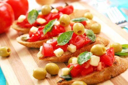 italian bruschetta with tomato and basil on wooden board photo