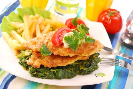 breaded sole on spinach with french fries for dinner photo