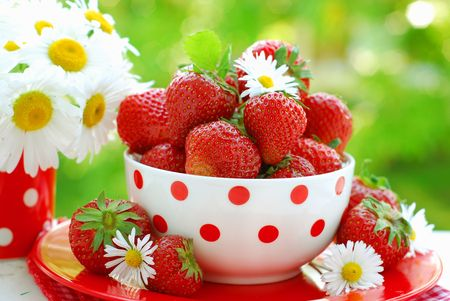 bowl of fresh strawberries on table in the garden photo
