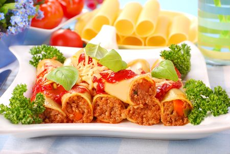 poured: italian cannelloni stuffed with minced meat  poured tomato sauce Stock Photo