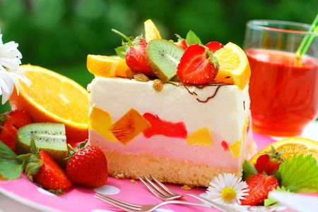 sliced fruit marshmallow cake with jelly on table in the garden photo
