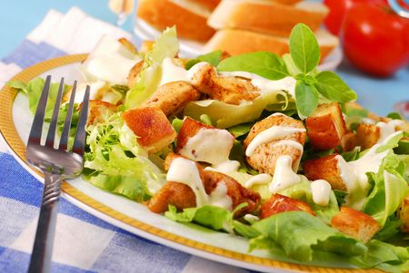 chicken caesar salad: bowl of caesar salad with lettuce,grilled chicken and croutons