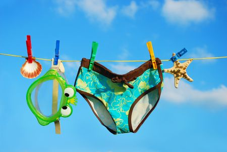 bikini pool: summer vacations accessories hanging on clothesline against blue sky Stock Photo