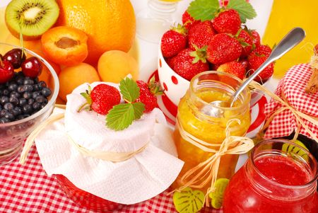 various fruits preserves in jars and fresh fruits on table  photo