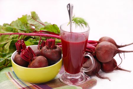 beets: fresh beets with leaves and clear soup in tall glass isolated on white