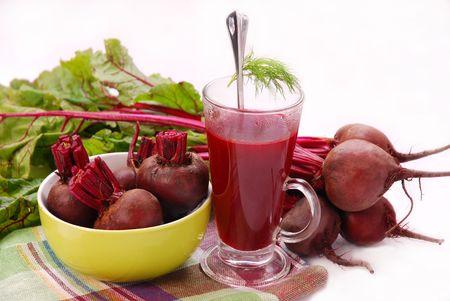 remolacha: remolacha fresca con hojas y sopa clara en vaso aislado en blanco