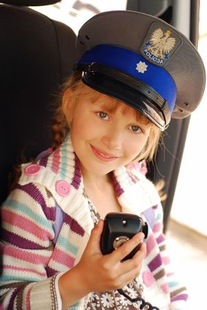 young girl wearing polish police hat holding radio in car photo