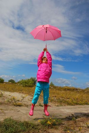 young girl keeping pink umbrella high up in the air above the sky and jumping photo
