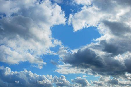 cloudy sky with heart shape blue  hole Stock Photo