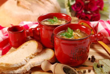 offal: traditional polish tripe soup with vegetables in red ramekin Stock Photo