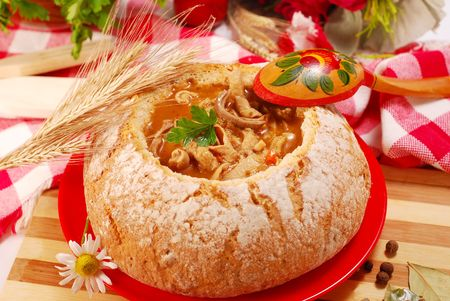 offal: traditional polish tripe soup with tomato and  vegetables in bread bowl