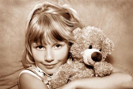 vintage teddy bears: Ritratto di giovane ragazza con il suo orsacchiotto in stile vintage (seppia)