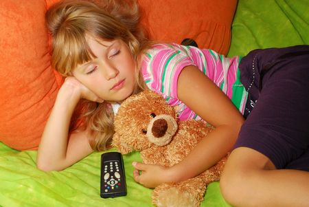 napping: young girl which fell asleep with her teddy bear watching tv Stock Photo
