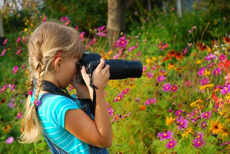 young girl taking photos by professional digital camera in autumn garden photo