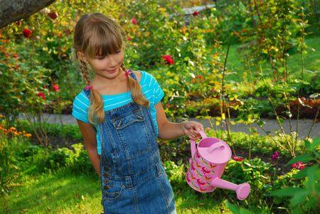 young girl  watering flowers in the garden with pink can