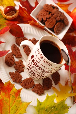 autumn cup of coffee and small chocolate  cakes in  shape of leaves
