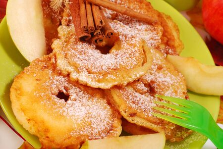 butter icing: apple fritters with icing sugar and cinnamon fried on pan for child